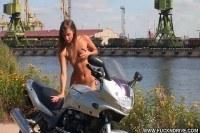 Голая девушка позирует на мотоцикле